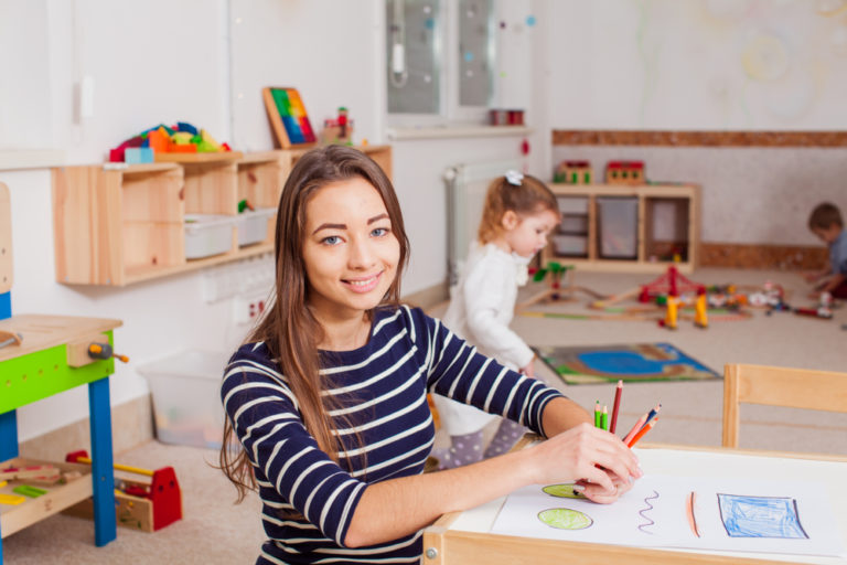 Teacher sitting at desk in kindergarten classroom