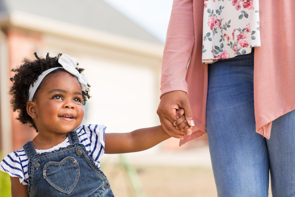 Little girl holding hands with her mother