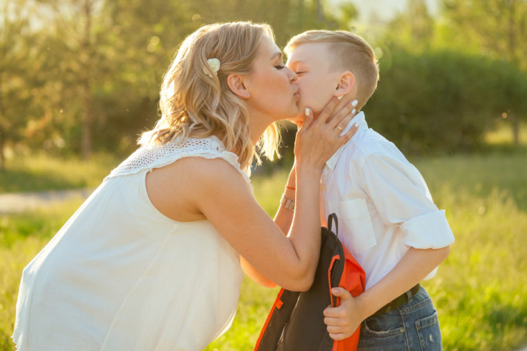 Mother hugging son on first day of school