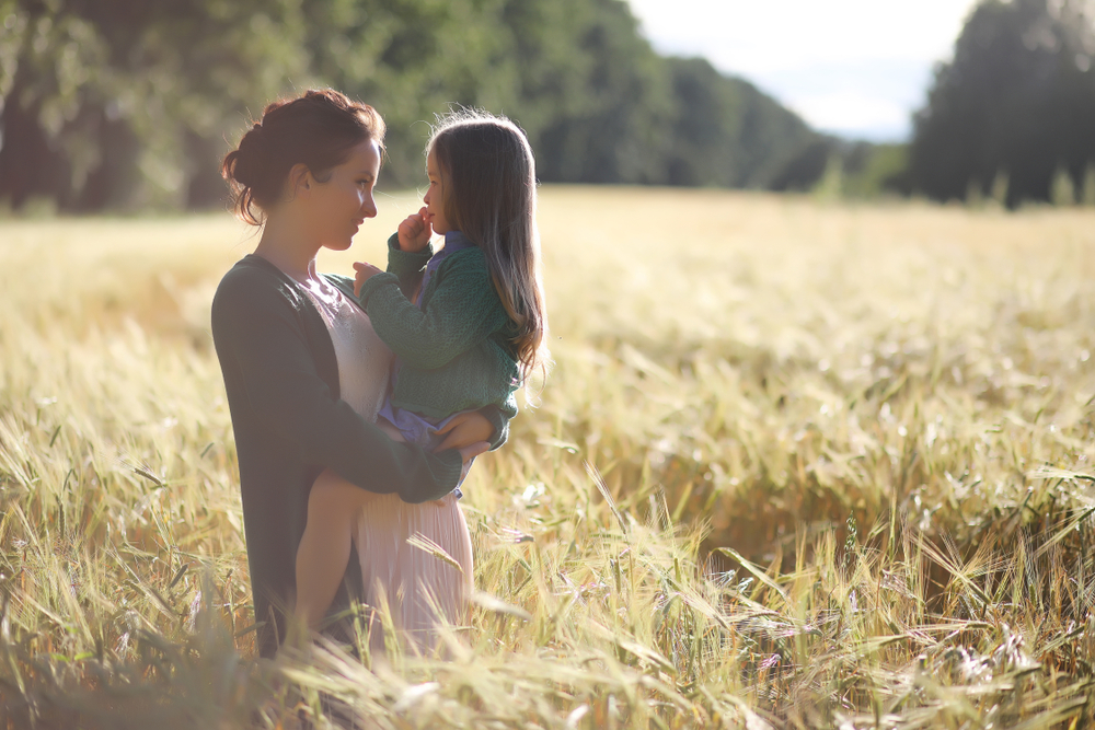 Mother and daughter standing in wheat field