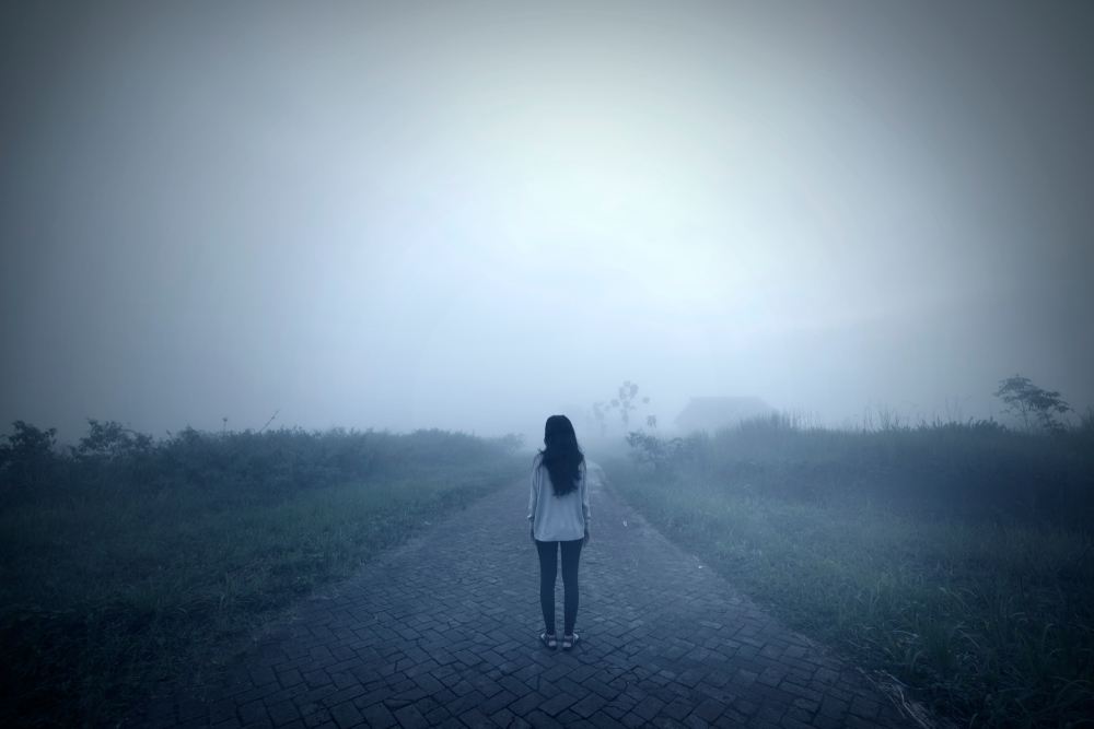 Woman standing in a road alone in the mist
