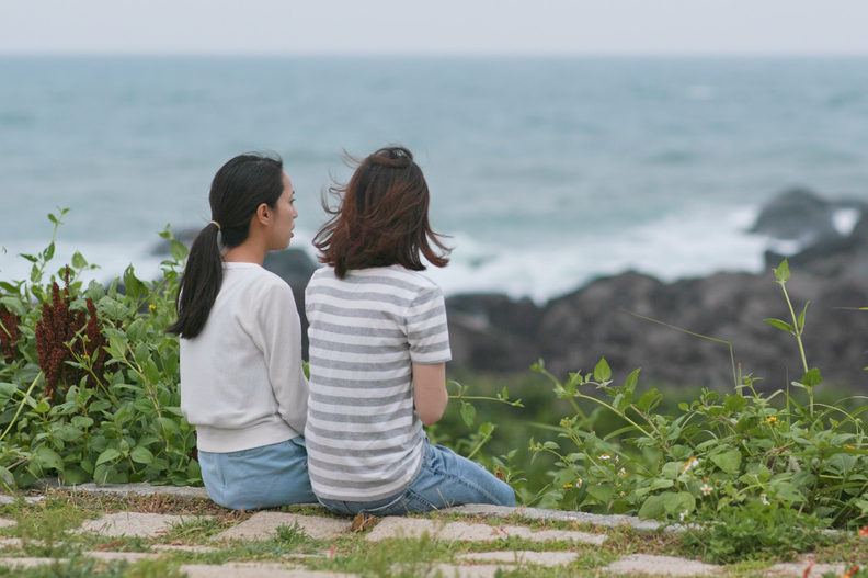 Two women sitting by the ocean