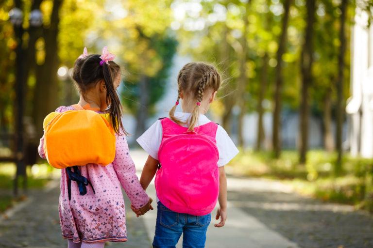 Two kindergarten girls walking to school with backpacks