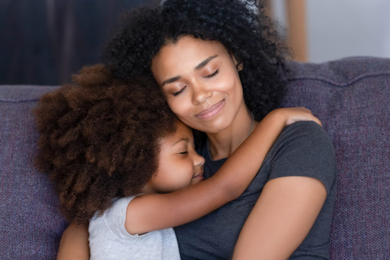 Mother and child hugging with eyes closed on couch