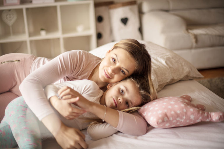 Mother hugging young child on bed at home
