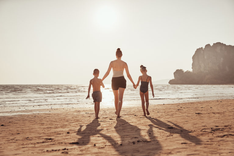 Single mother walking on beach with two kids