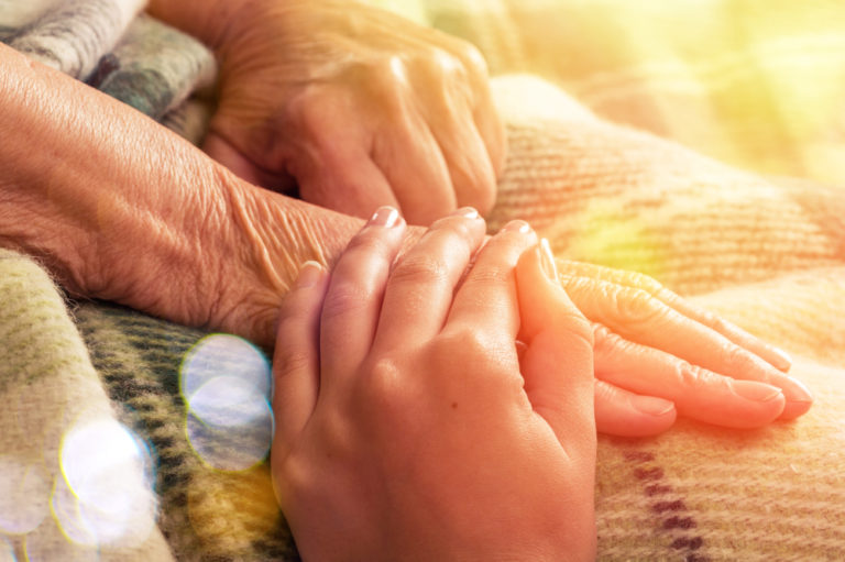 Elderly woman's hands being held on blanket with sun flare
