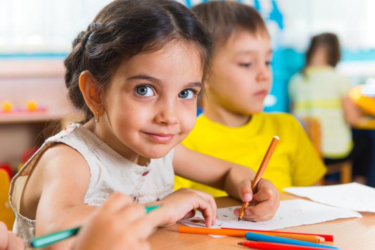 Kindergarten student sitting at desk with pencils