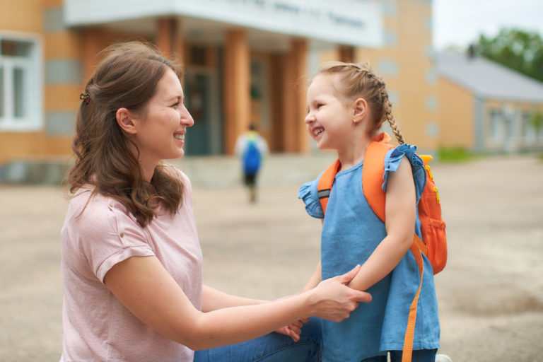 Kindergartener and mom smile at each other in front of school