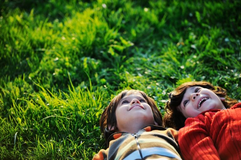Two cousins laying in the grass together smiling