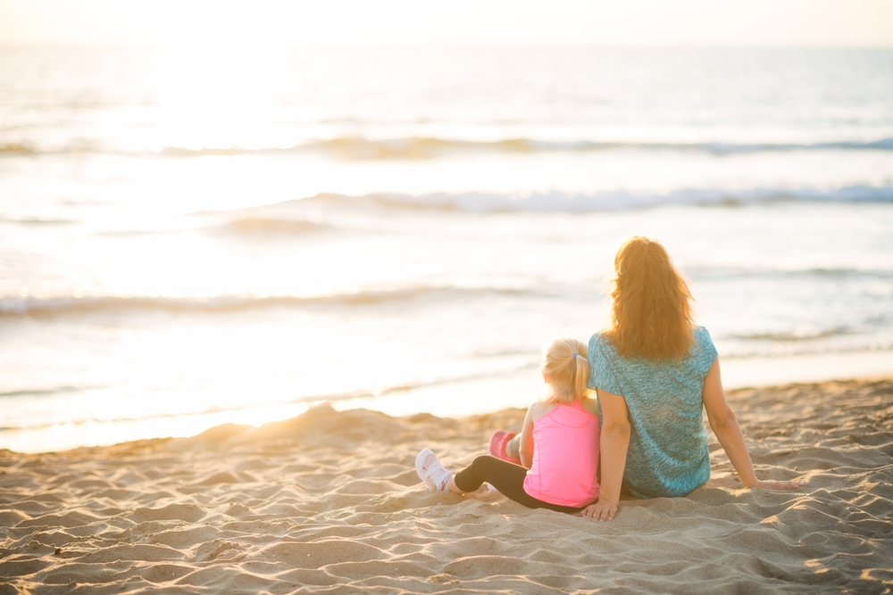 Mother and daughter sitting on beach at sunset