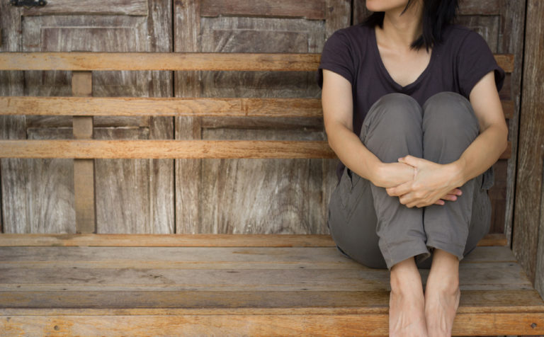 Woman sitting alone holding knees on bench