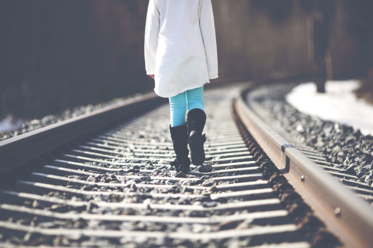 Woman walking alone on tracks
