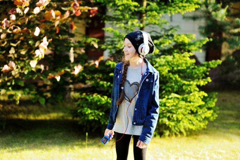 Tween girl wearing headphones and hat