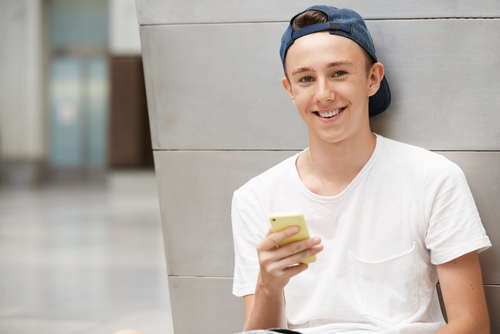 young teen boy holding cell phone