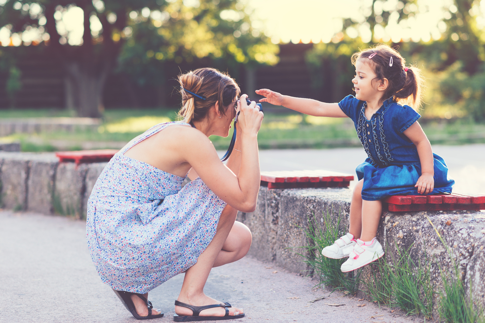 Mother taking photo of her daughter