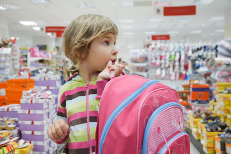 Little girl back to school shopping with backpack