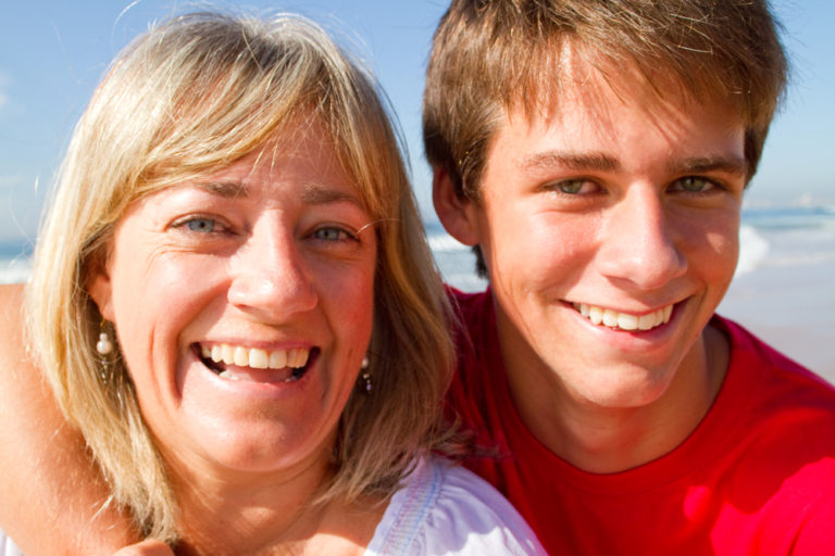 Mother and grown son smiling at camera