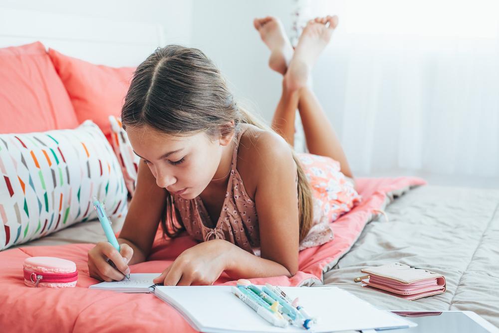 tween girl writing in journal in her bedroom