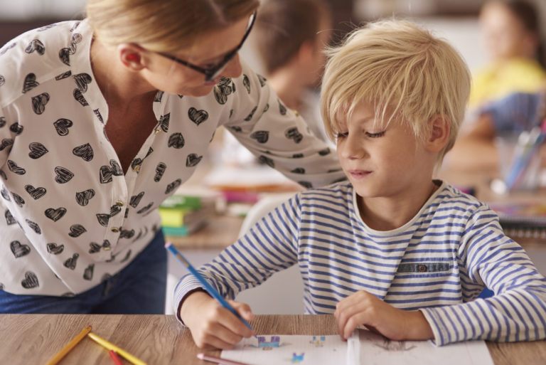 Teacher helps boy in classroom