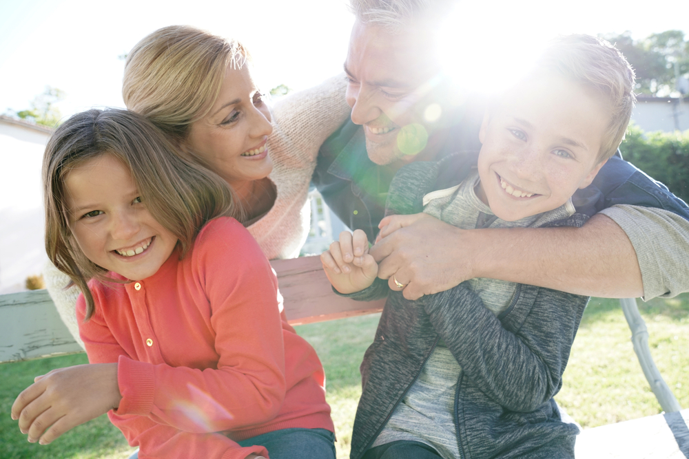 Family of four mom smiling at older kids