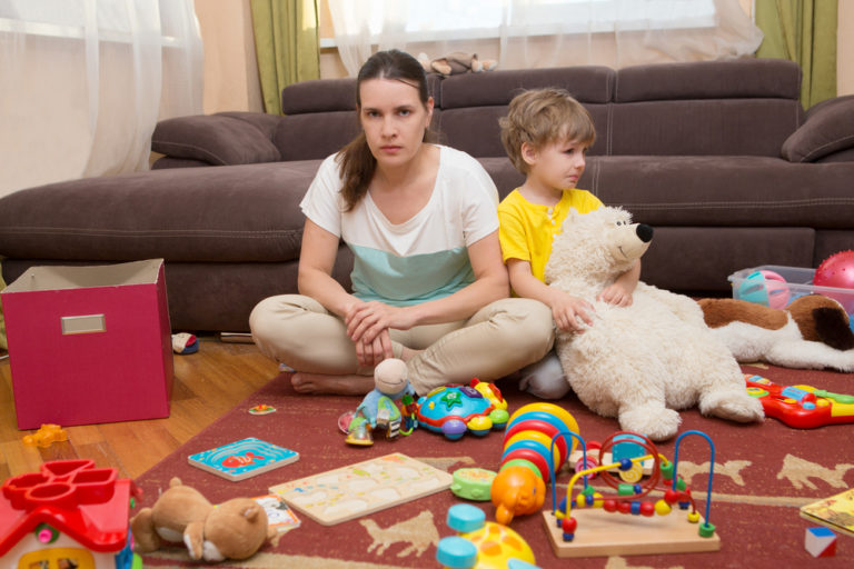 Tired mom sitting in messy living room with child