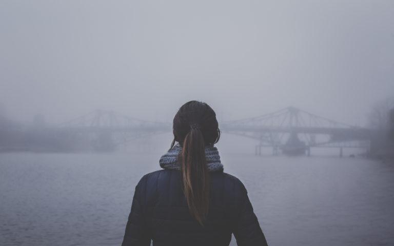 Woman standing in fog looking at bridge