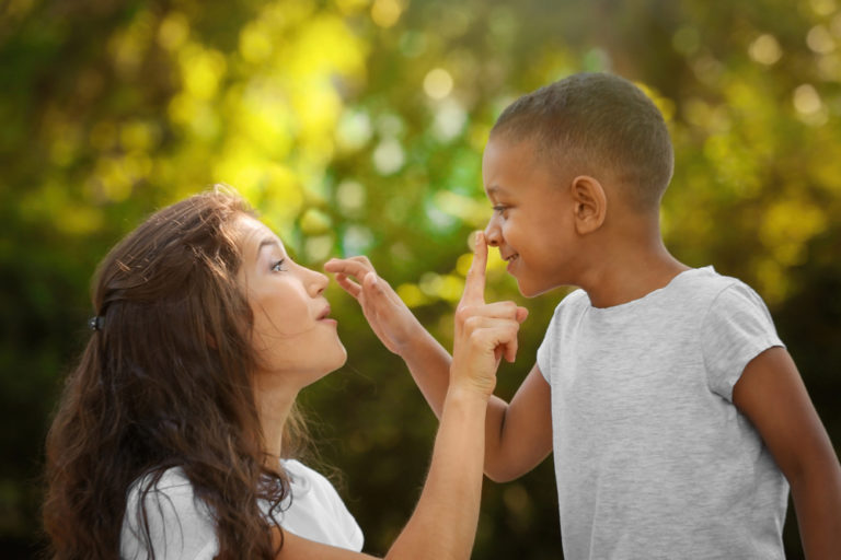 Mother touching her young son's nose and smiling