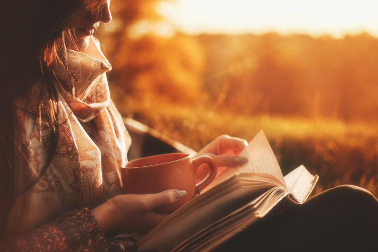 Mother reading in evening light with coffee and book