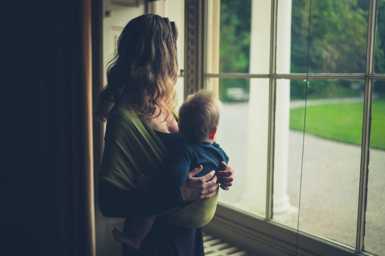 Mother holding toddler on hip looking out window