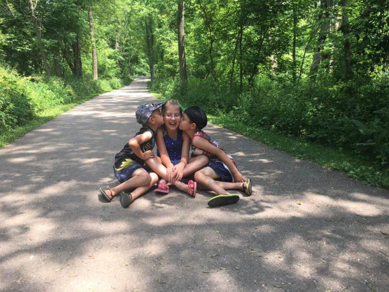 Three children sitting on ground