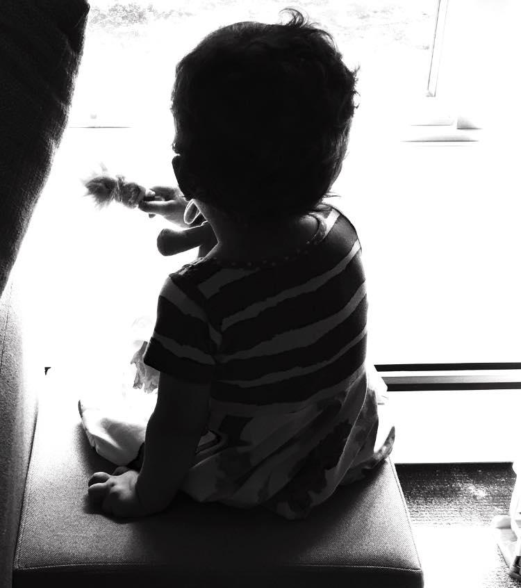 Little boy looking out window