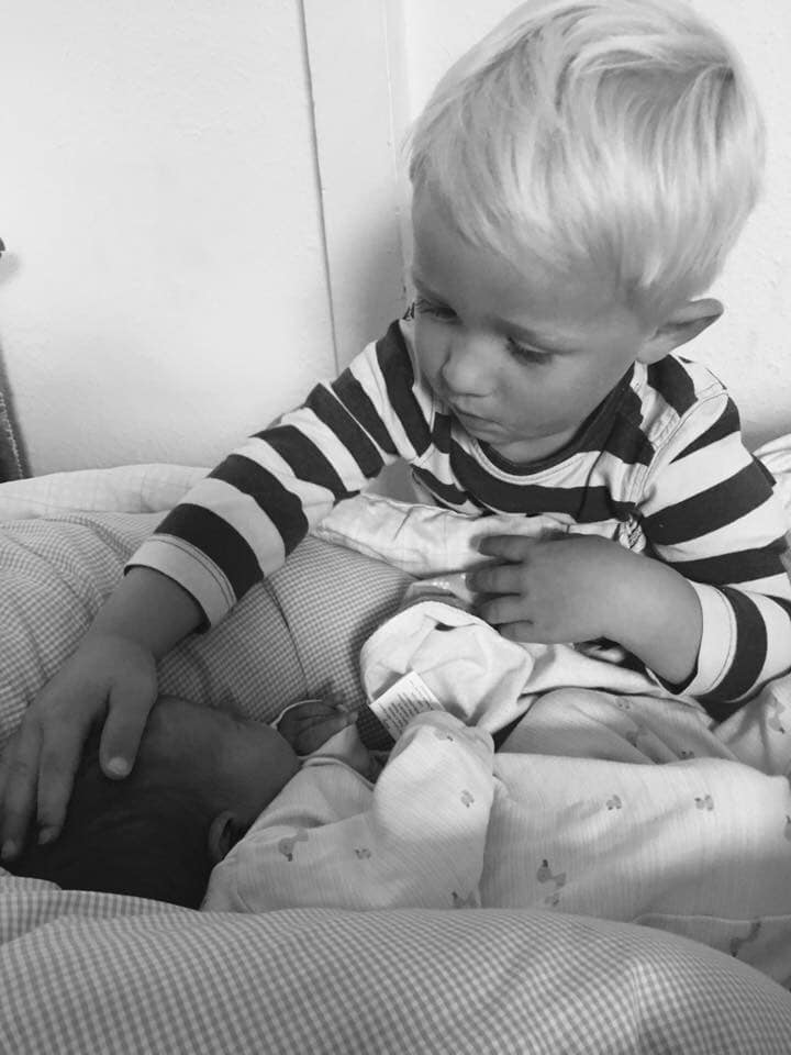 Little boy playing with new baby