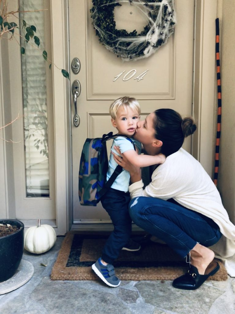 Mother kissing son on front step