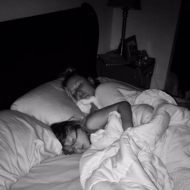 Mother and child asleep in bed