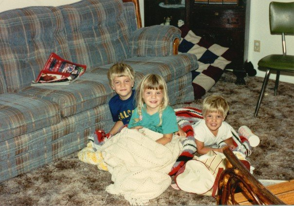 Three kids on the floor with blankets