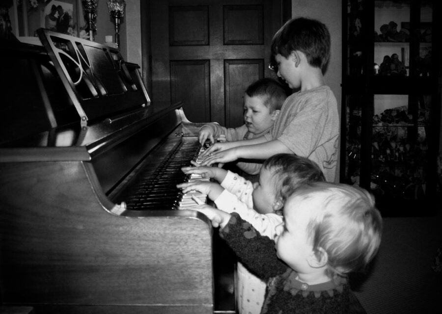 Four kids at piano black and white photo