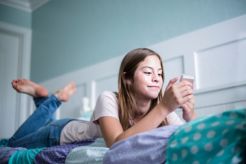 Tween with cell phone at home
