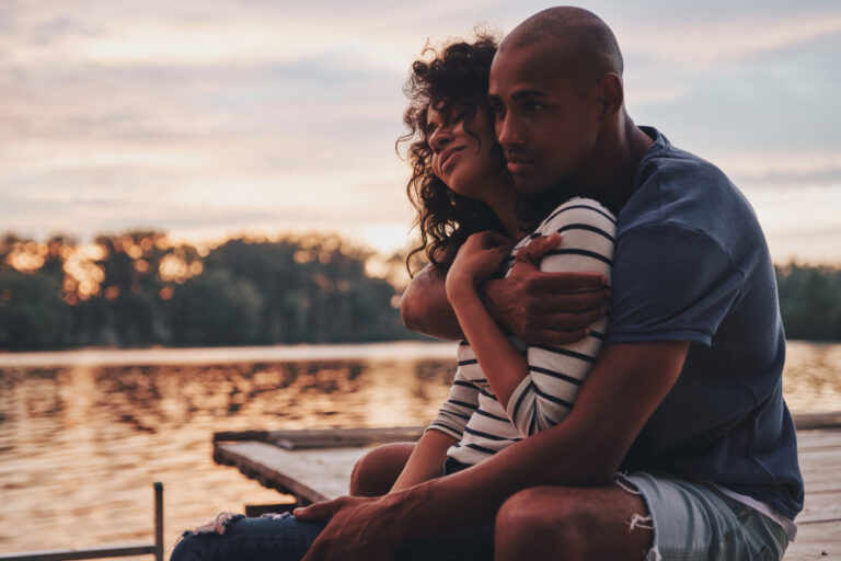 Couple sitting together on dock at sunset