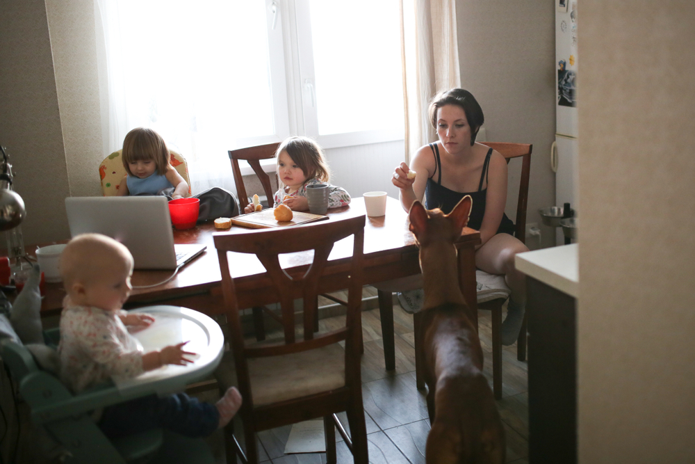 Tired mother sitting in kitchen with kids and dog
