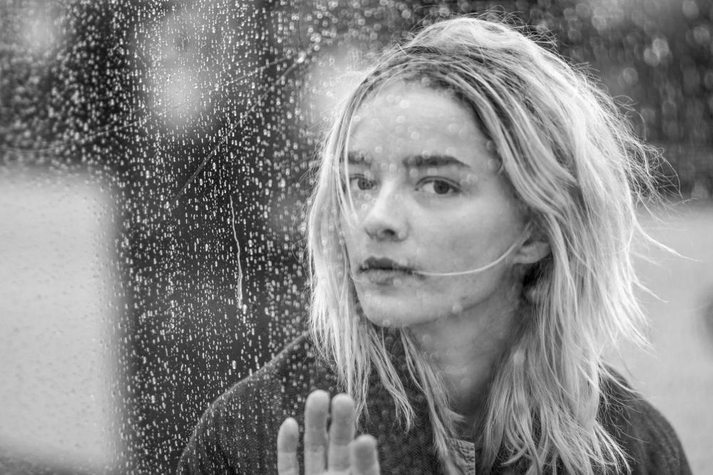Woman in window with rain