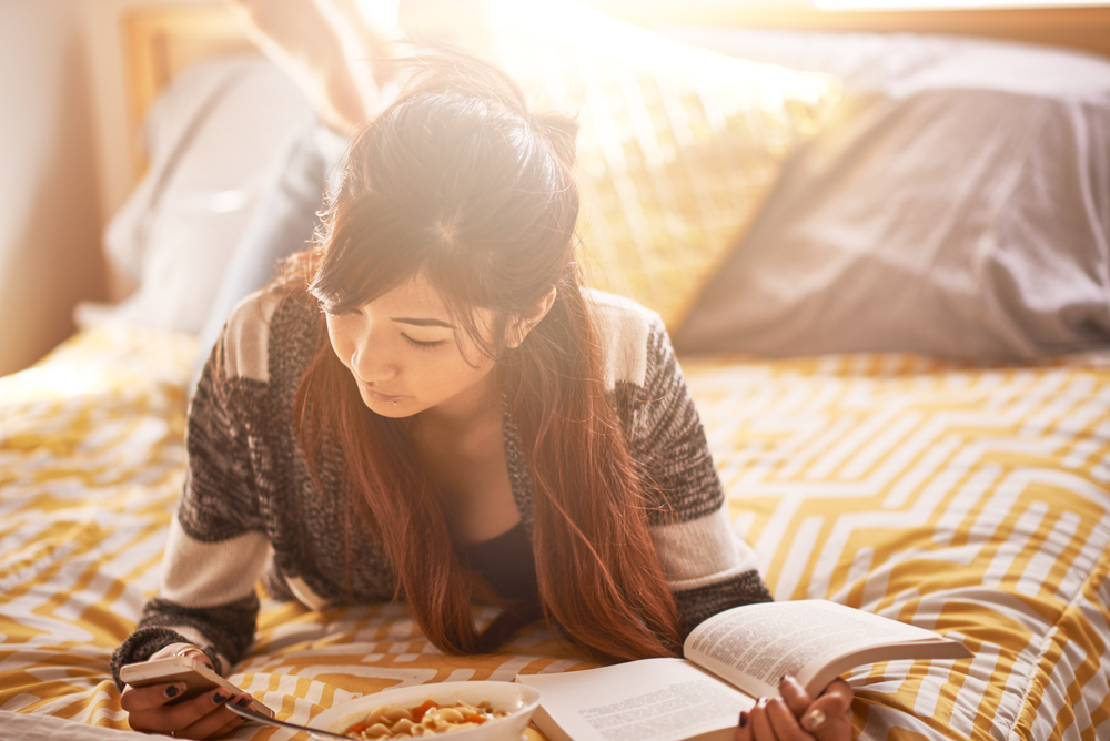 Teen girl writing in journal on bed
