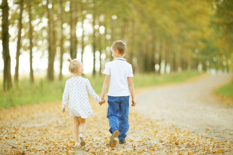 brother and sister holding hands walking