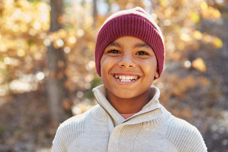 Tween boy smiling in the fall sun