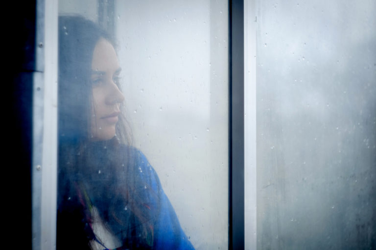 Woman looking out window at rain