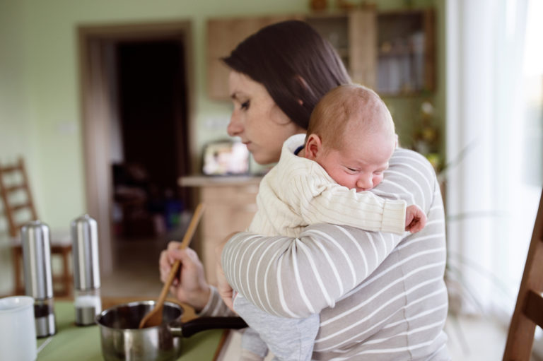 New mom holding infant while cooking