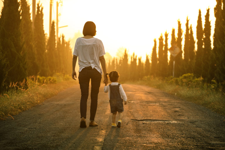 Mother and child walking down road at sunset