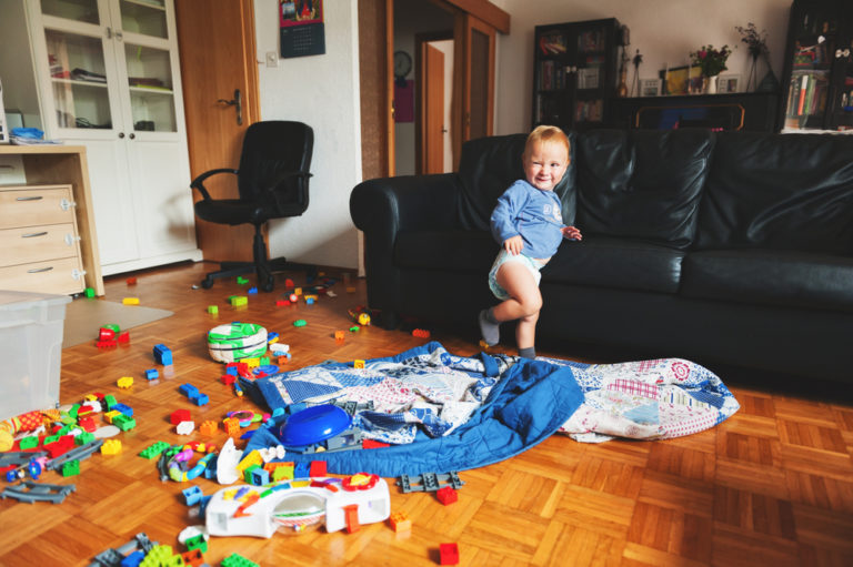 Toddler in messy living room with toys