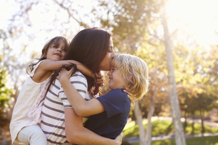 Mother kissing two children