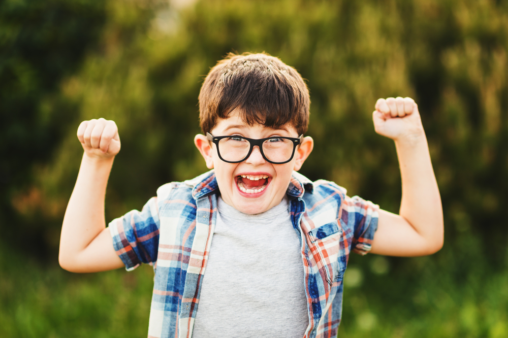 Little boy with glasses raising arms